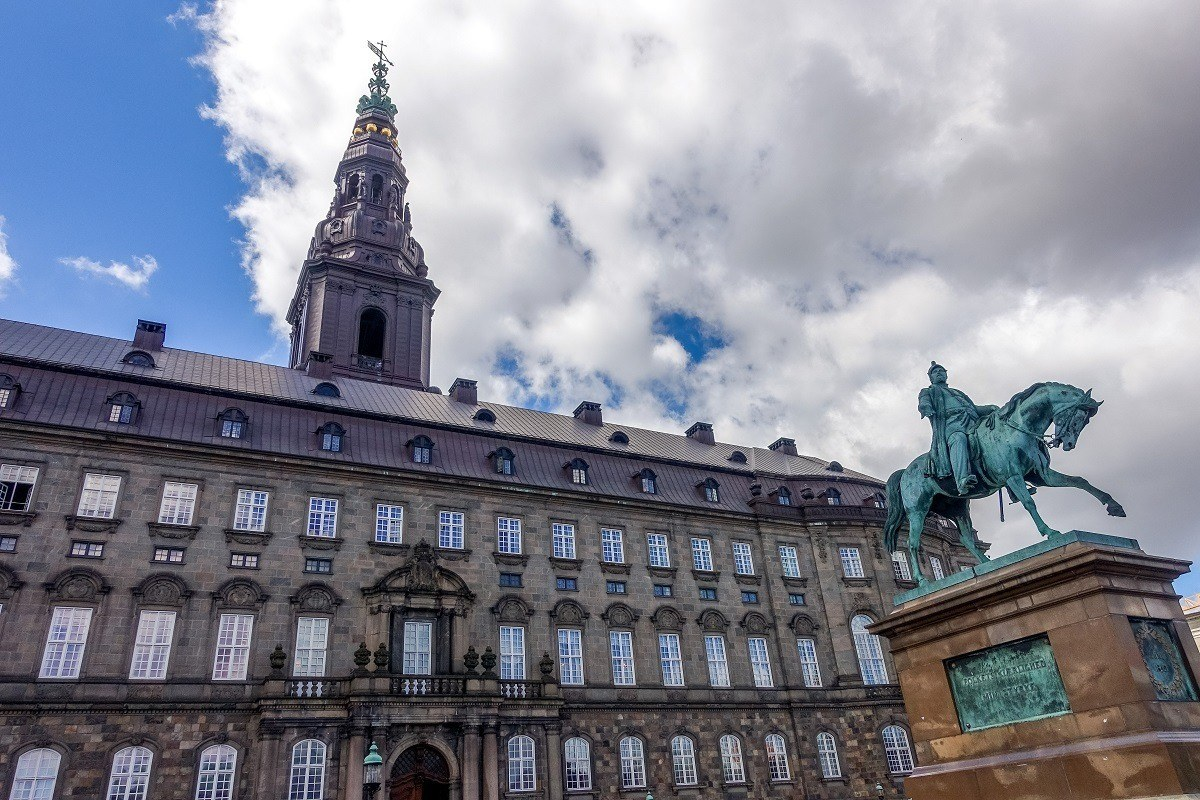 Statue of man on horse in front of a large building