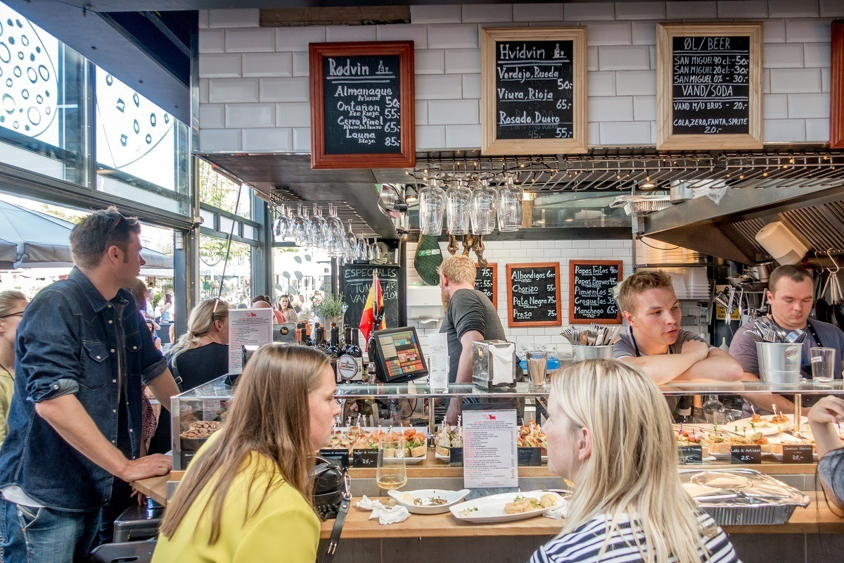 People eating at a stall in a food hall