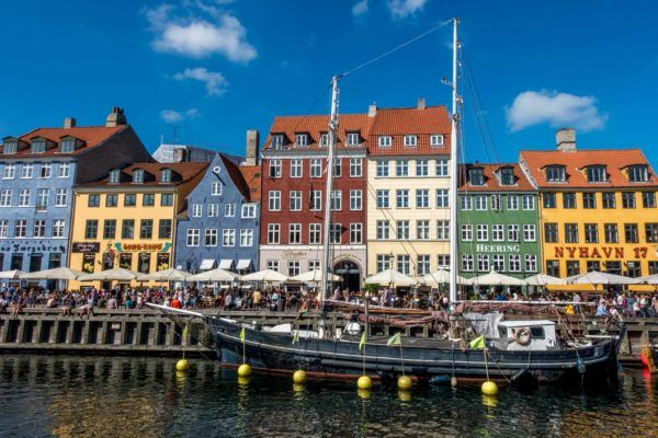 Brightly colored buildings and a boat in a Copenhagen harbor