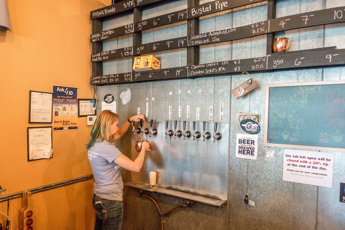 Woman pouring beer at Tin Cannon Brewery