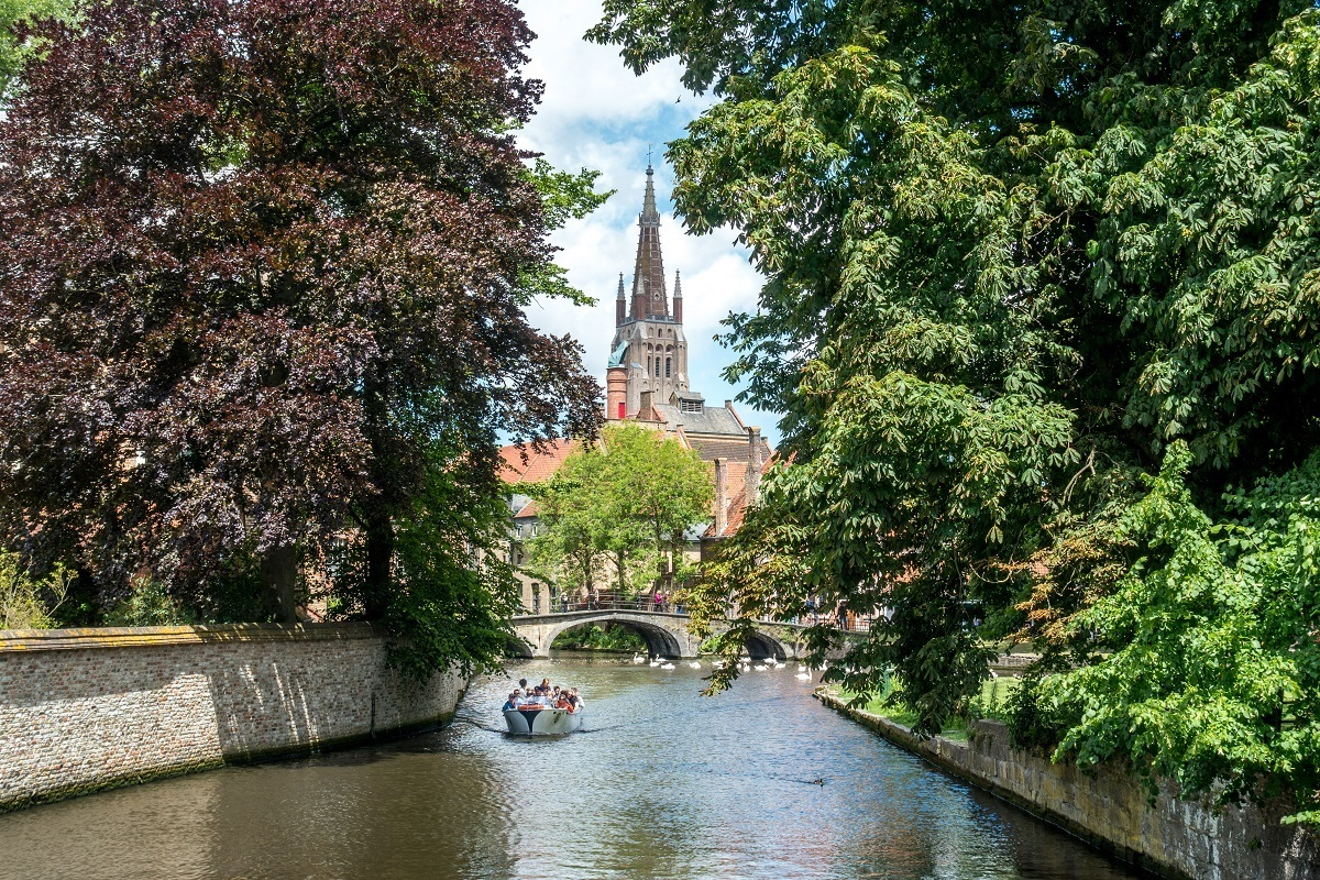 Boat cruising down one of the canals in Bruges, Belgium