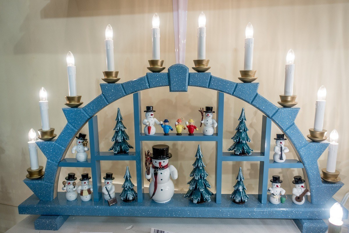German schwibbogen decoration with toy snowmen and electric candles