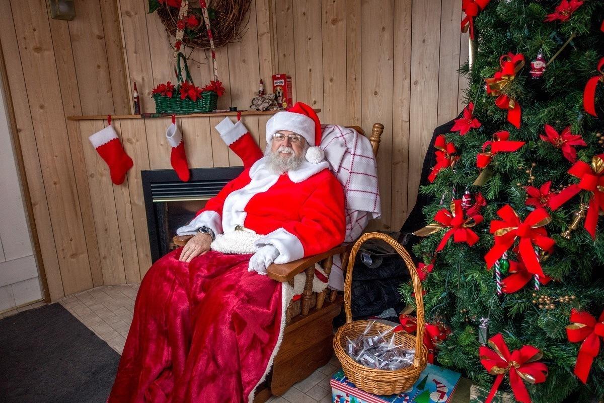 Santa sitting by a Christmas tree