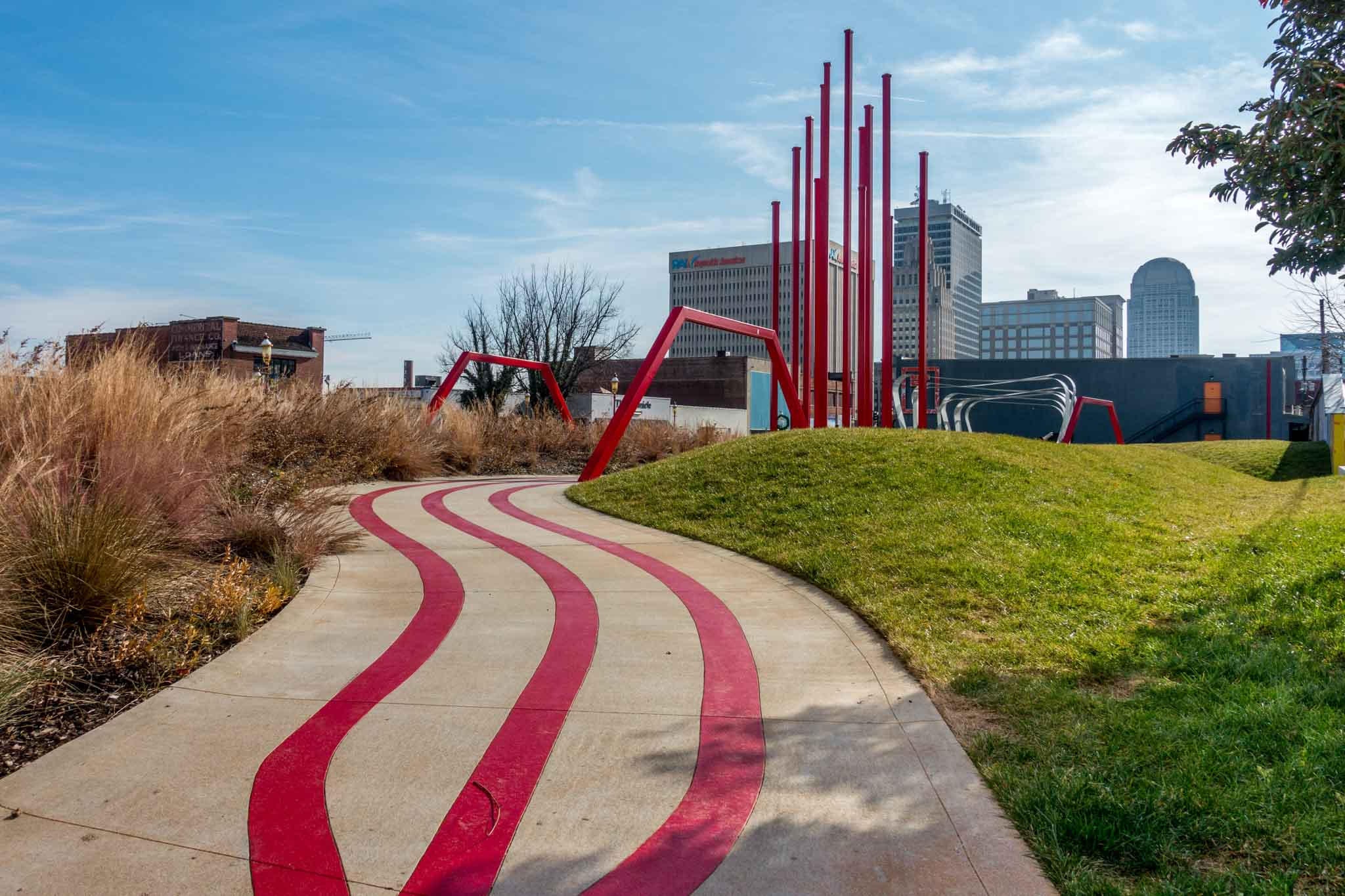 Outdoor artworks including a red sidewalk trail leading to a red sculpture