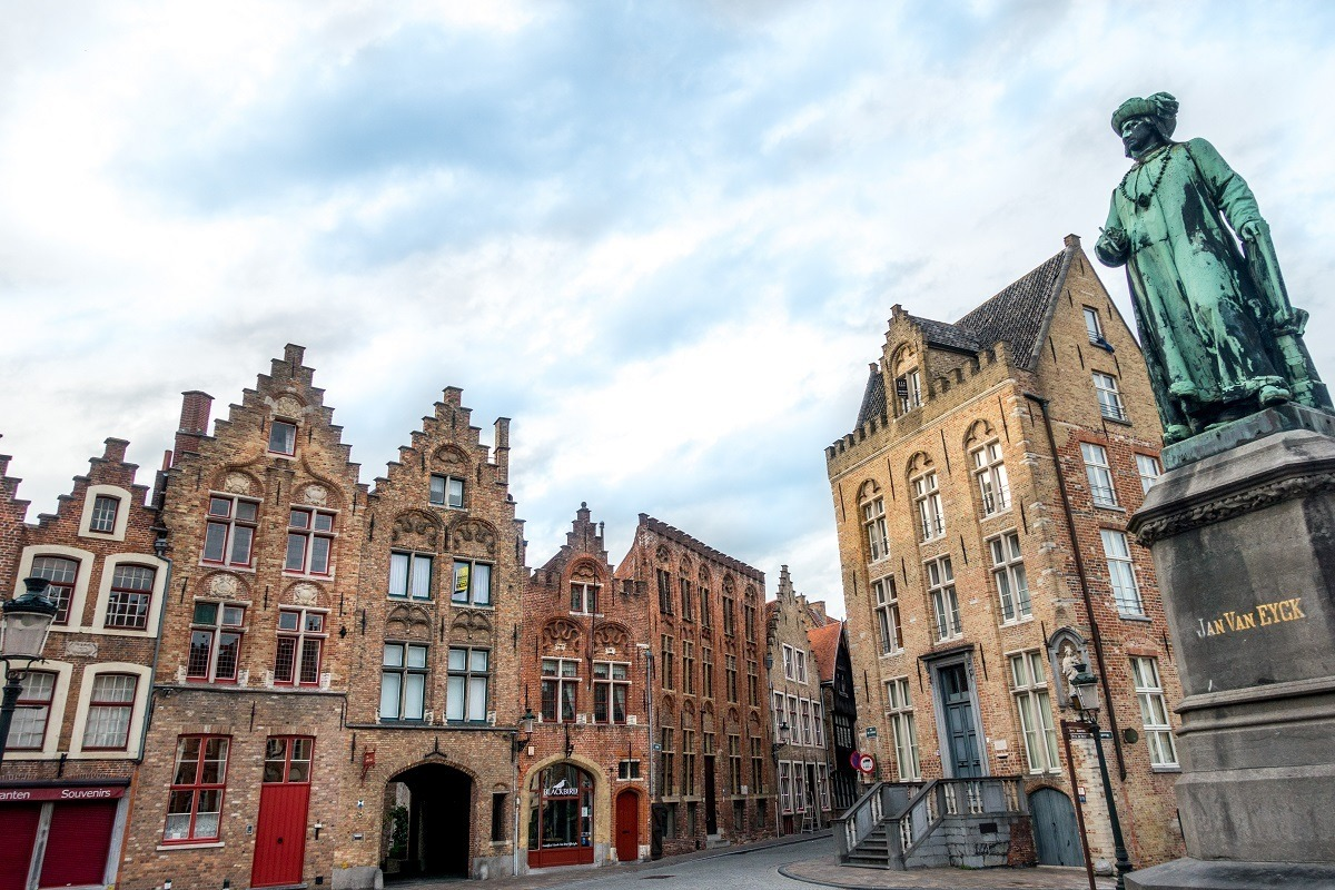 Statue of artist Jan Van Eyck and canal house