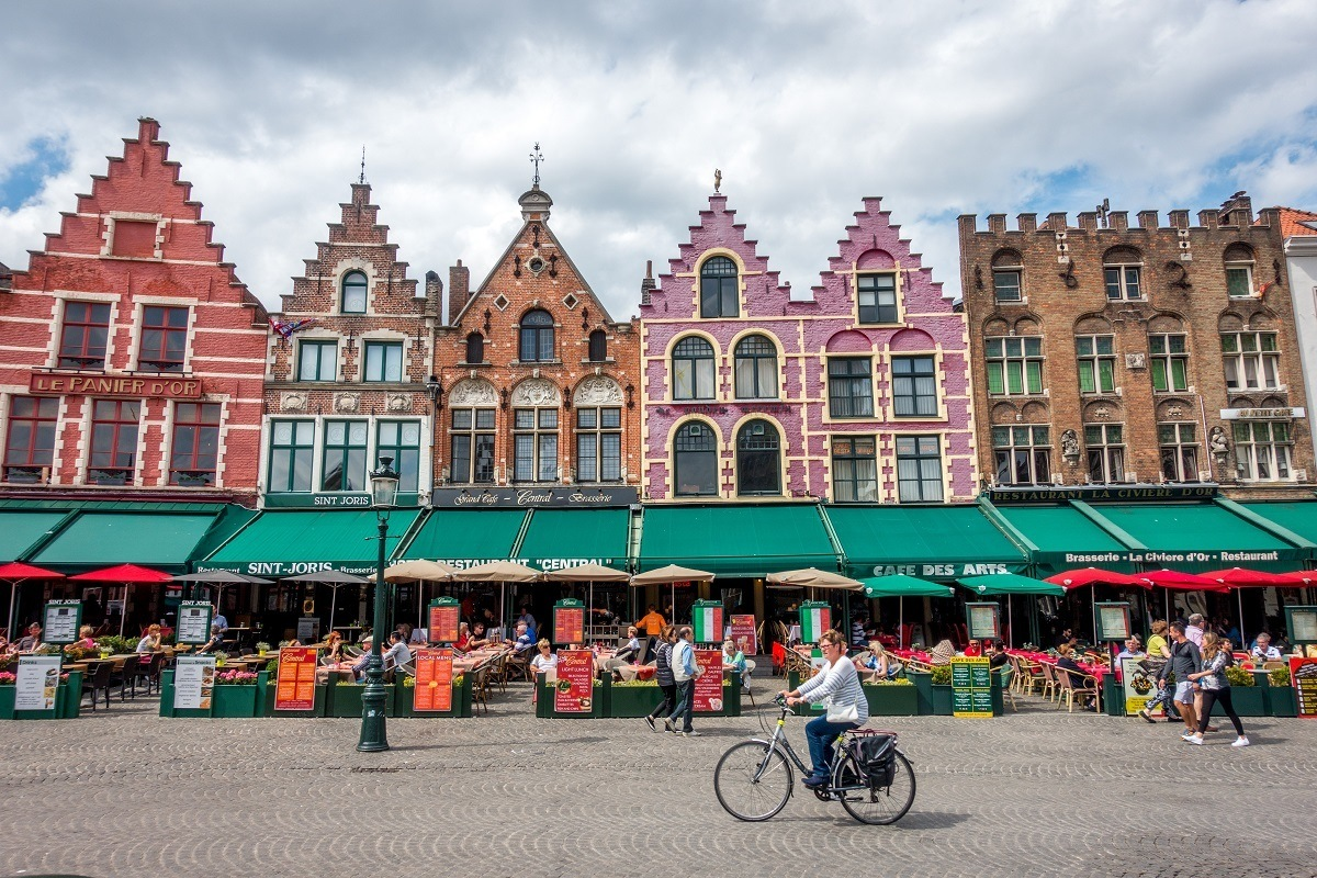 Person bicycling row of traditional buildings in Bruges