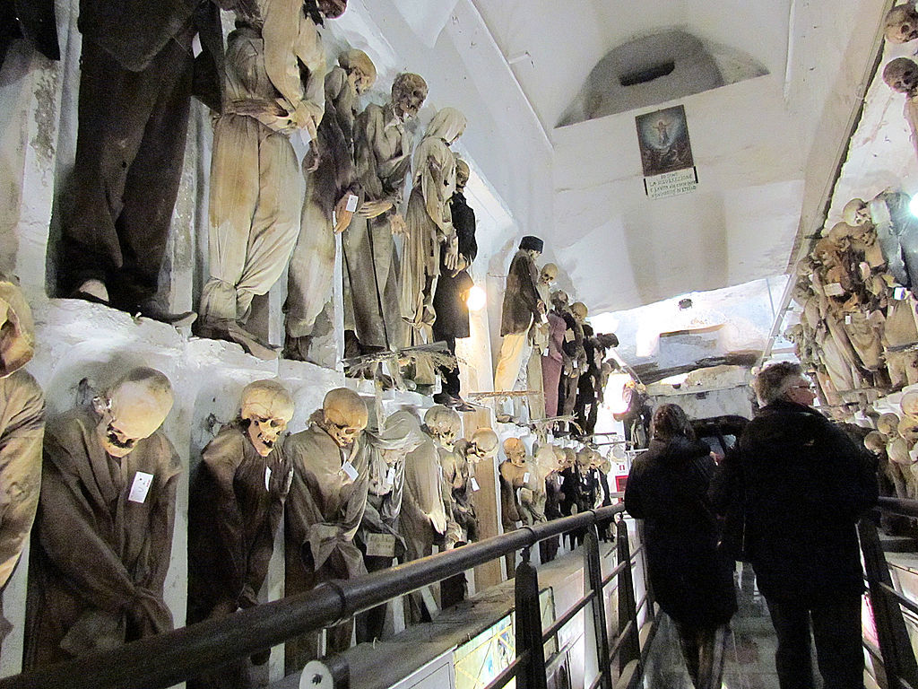 Skeletons and mummies line the walls of catacombs