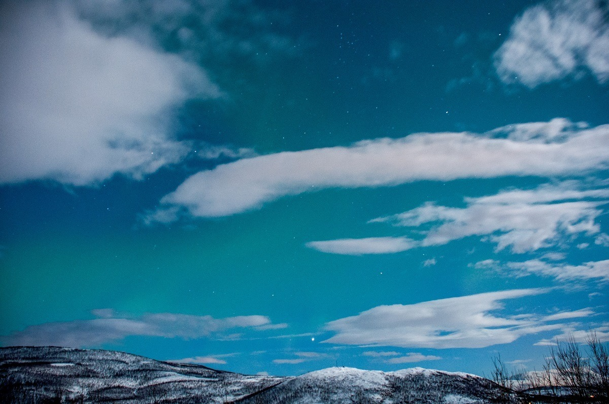 Slight green haze of aurora borealis in a cloudy sky