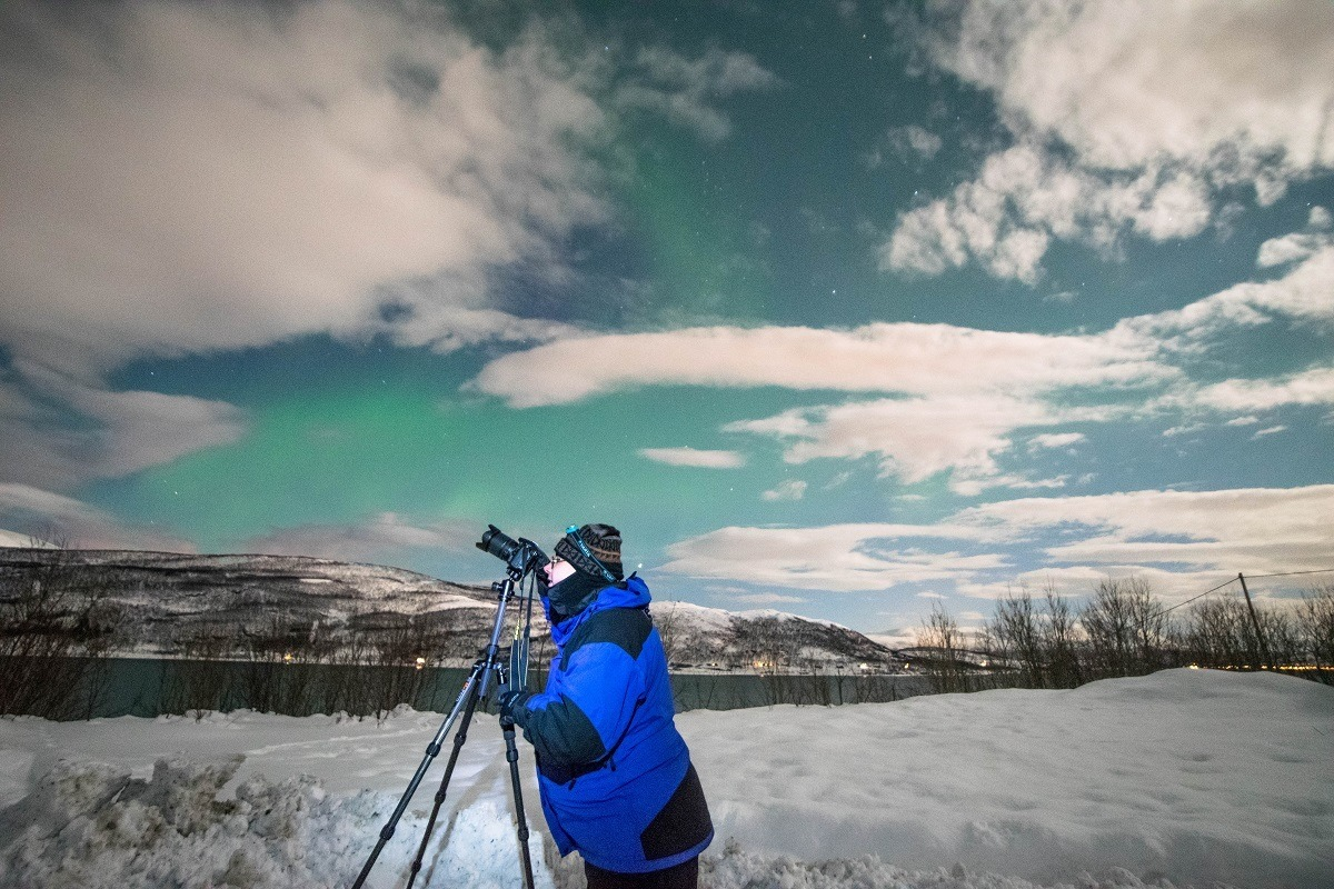 Lance looking into his camera while photographing the northern lights in Tromso