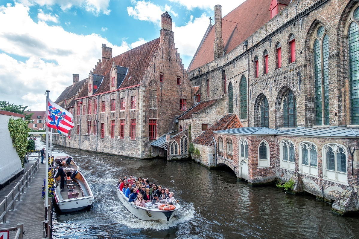 Boat in canal in Bruges, Belgium. Which is better—Ghent or Bruges?