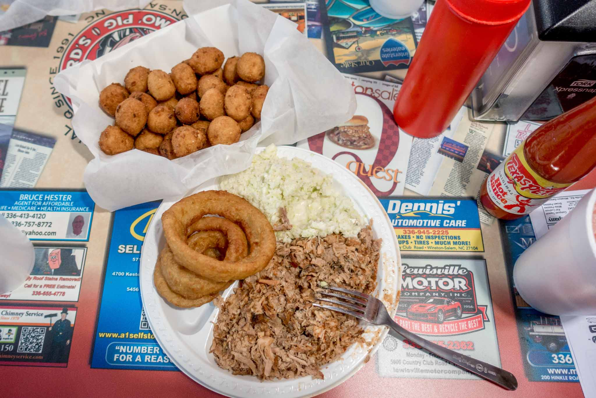 Barbecue, onion rings, and hush puppies on plates