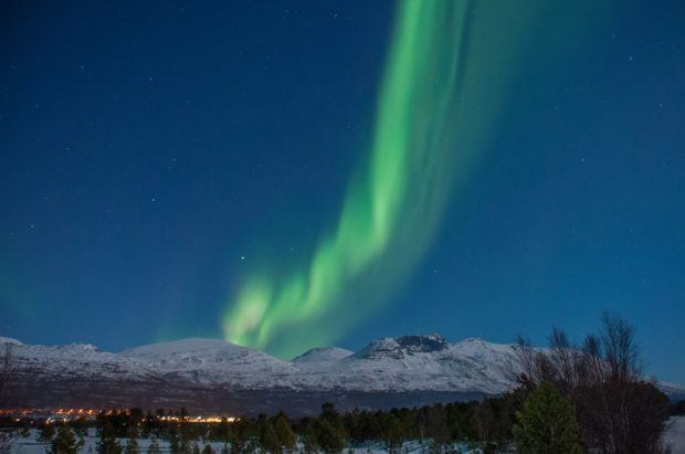 Wisp of green light over a snow-covered mountain