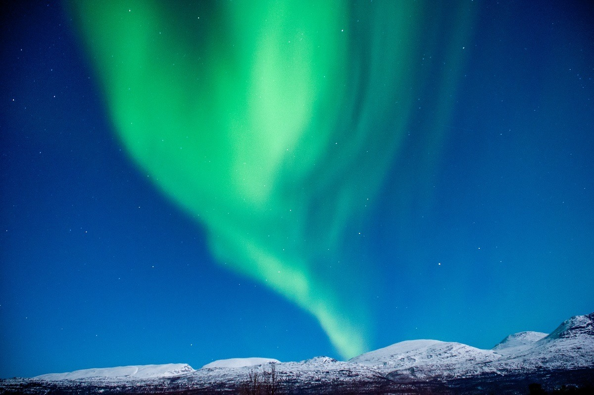 Green Northern Lights display over snowy hills