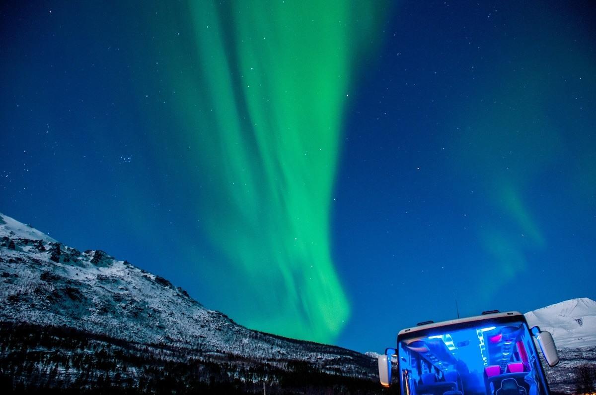 The aurora borealis visible above a Northern Lights Tour bus