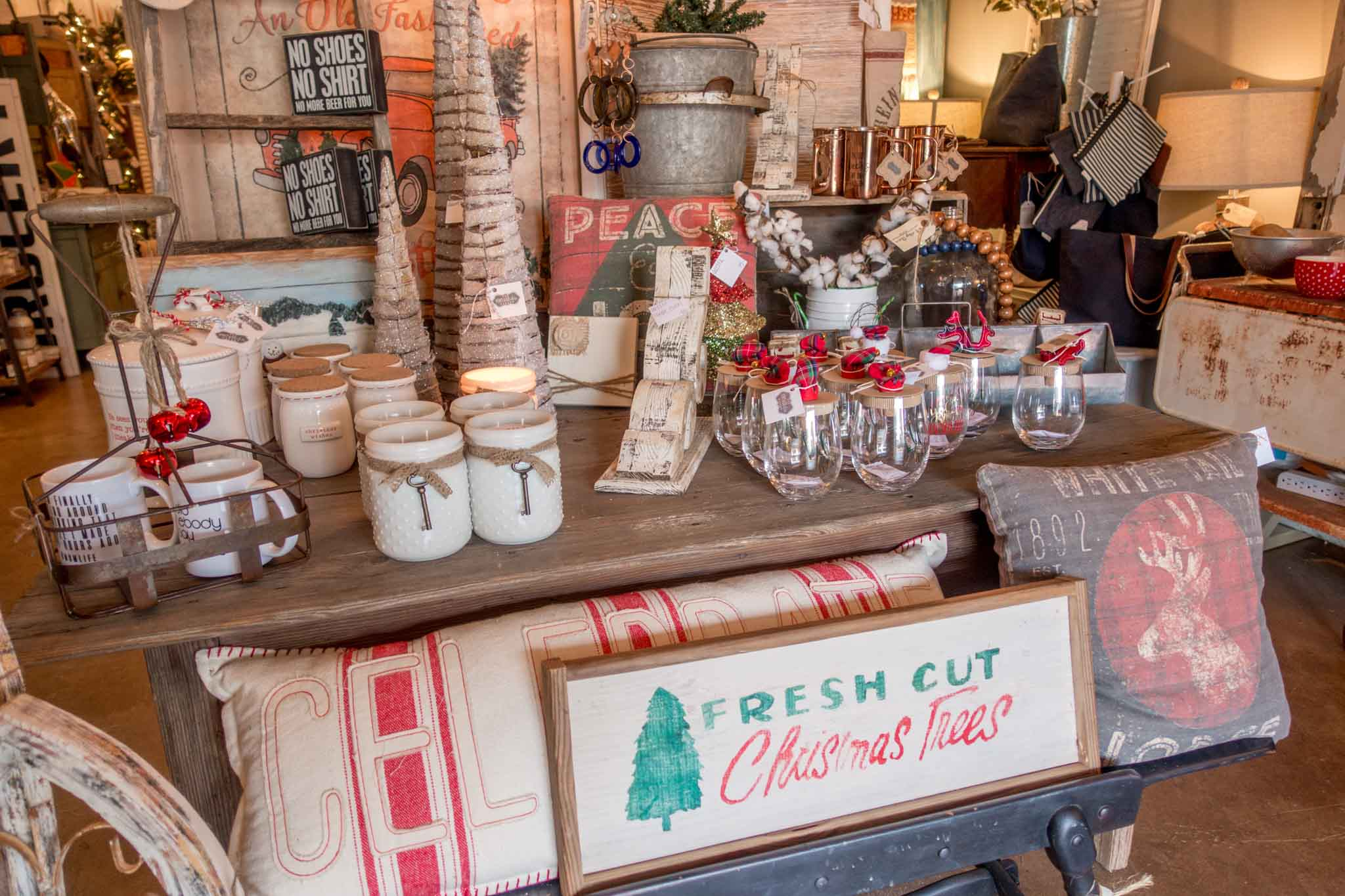 Mugs, pillows, and Christmas items for sale in a store