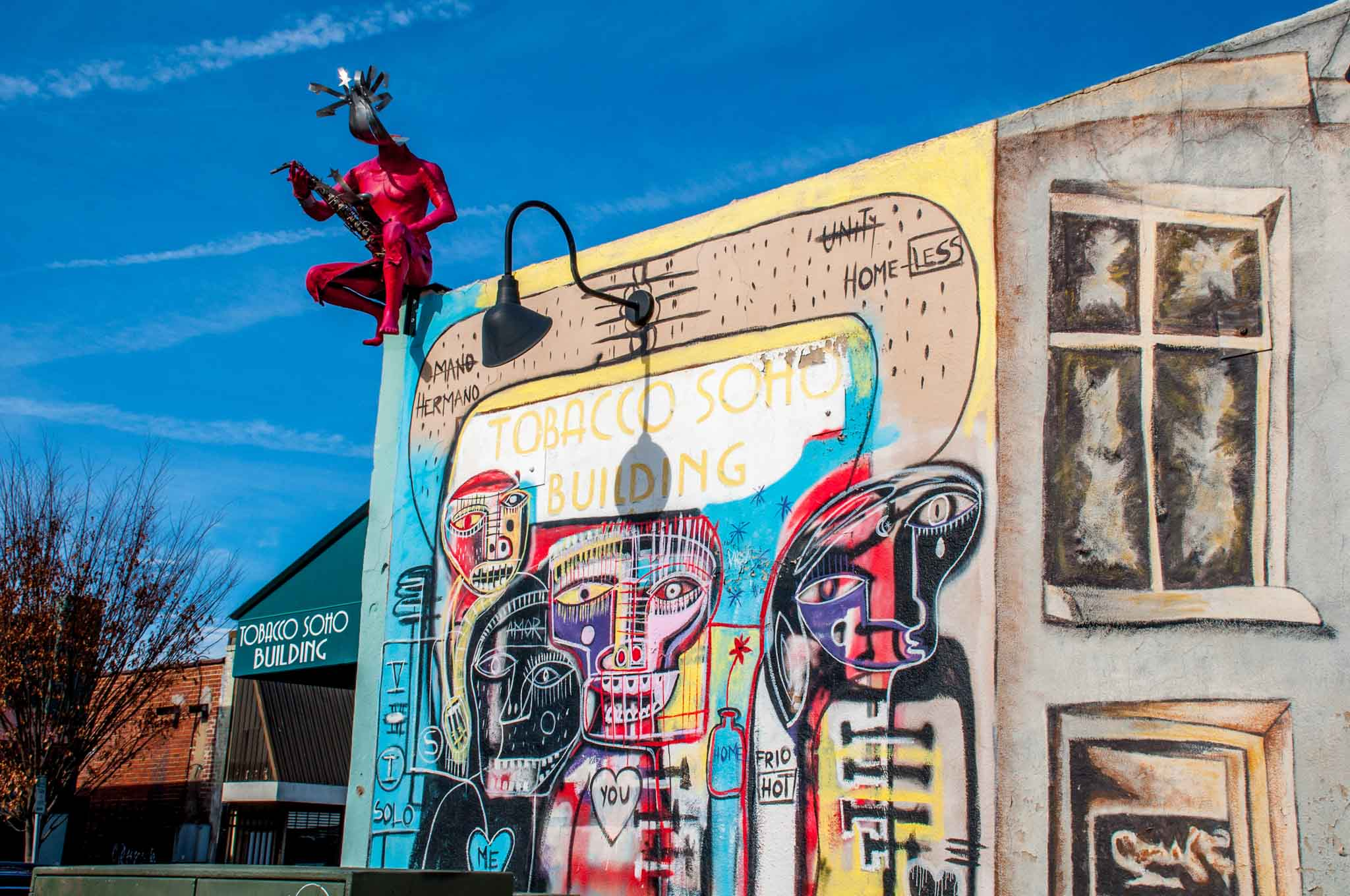 Street art mural showing colorful figures on the Tobacco Soho Building in Winston Salem NC