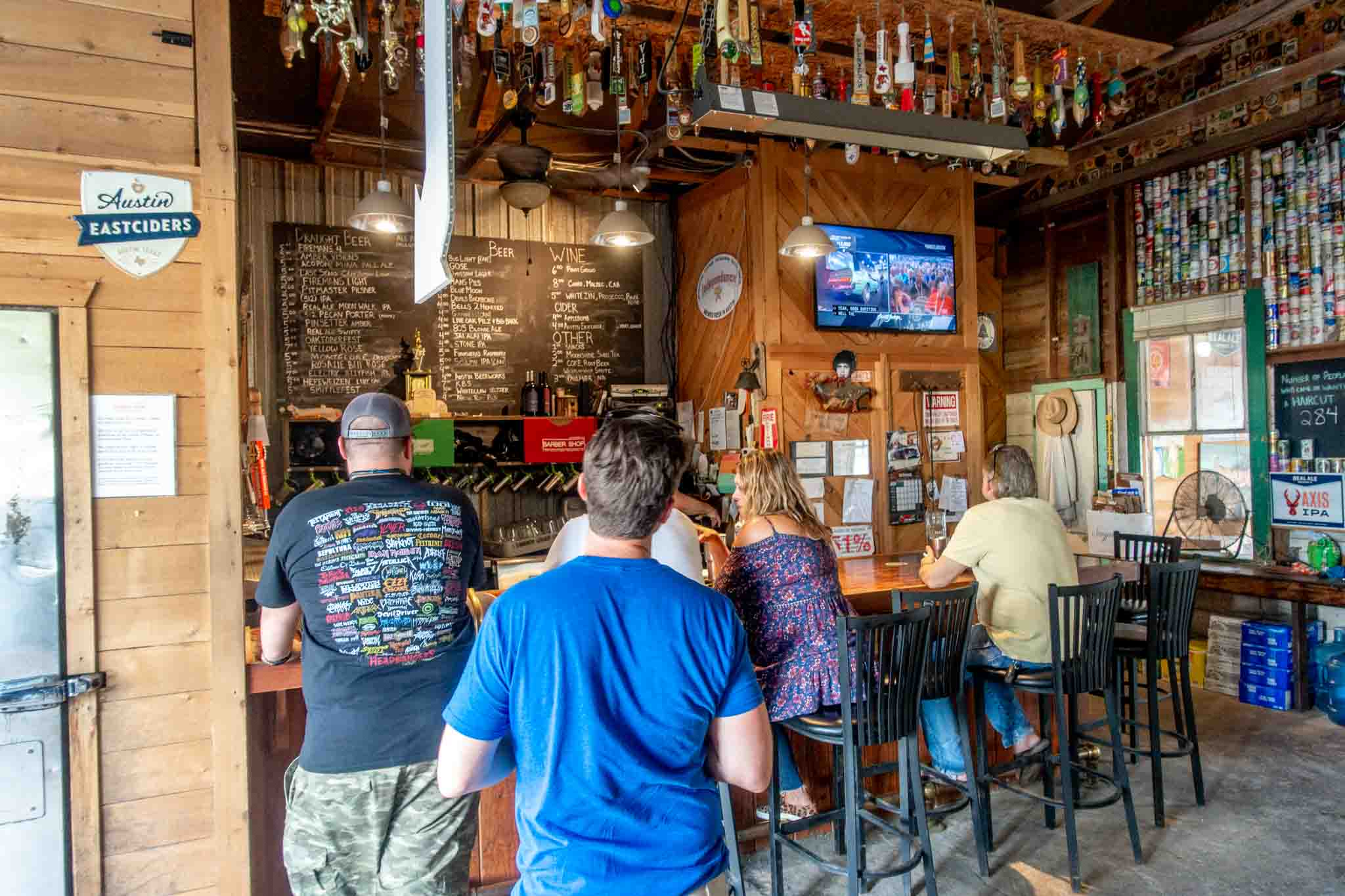 People at a bar ordering drinks and watching TV