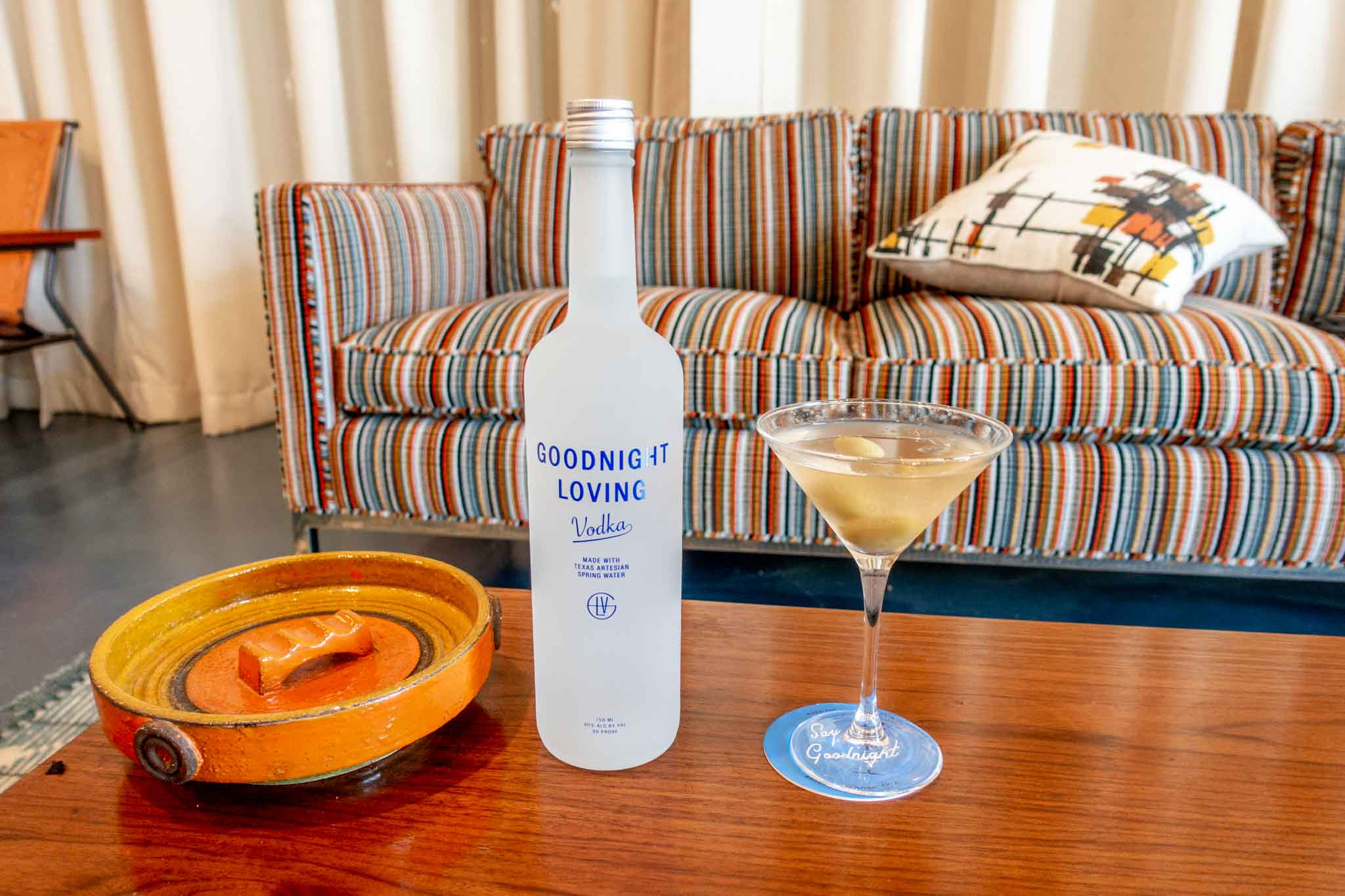Bottle of Goodnight Loving vodka and a martini in 1960s-inspired room