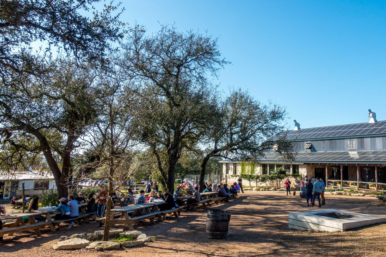 Visitors sitting at picnic tables and walking near barn