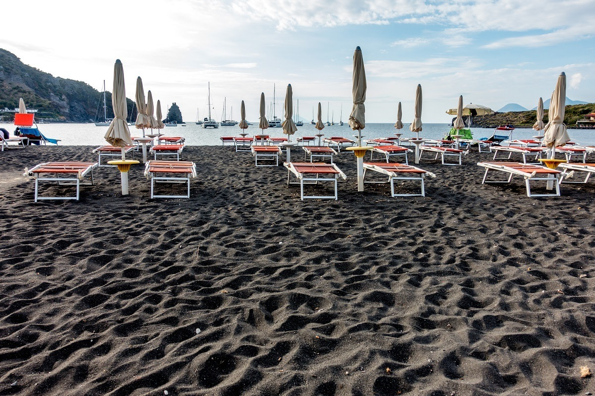 Lounge chairs for relaxing on the black sand beach on Vulcano