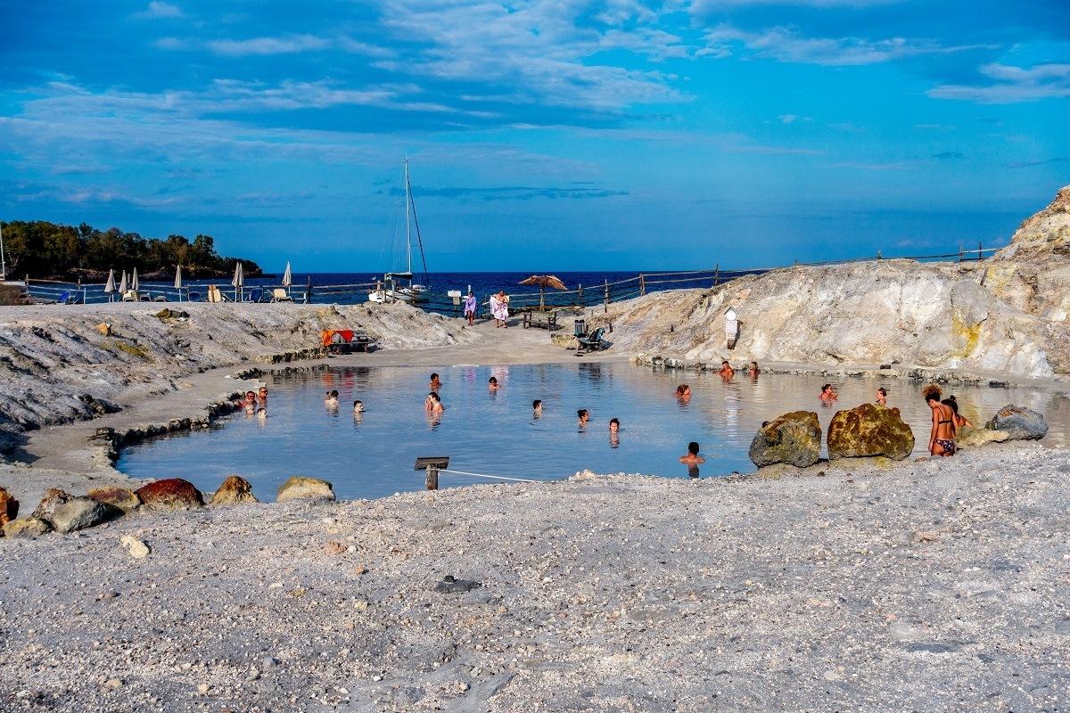 People soaking in the Vulcano Island mud baths in Italy.
