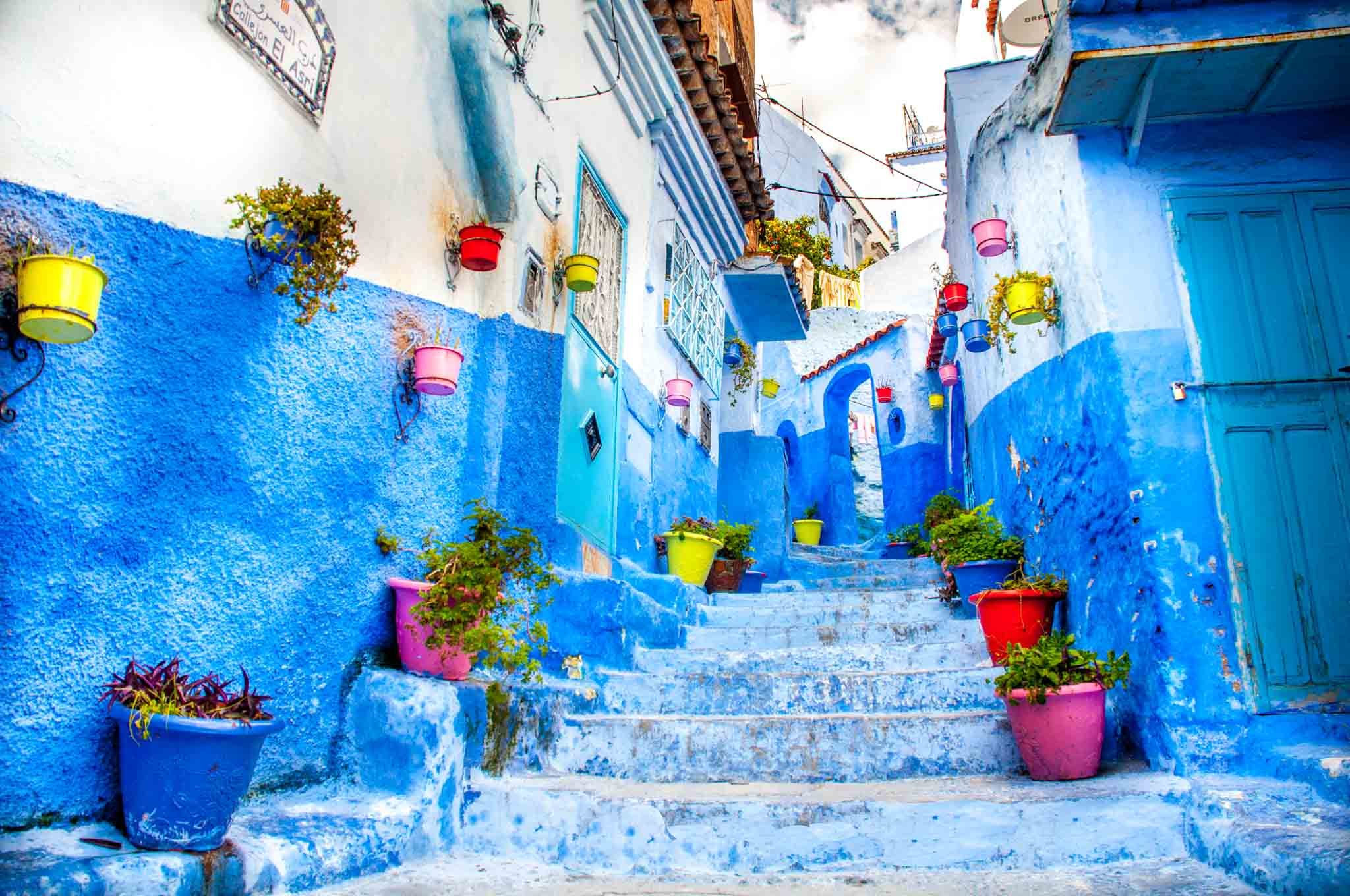 Blue staircase lined with colorful pots in Chefchaouen Morocco