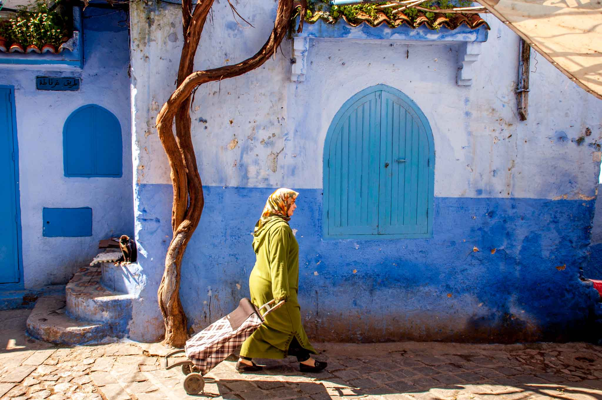 Woman walking by blue wall in Chefchaouen, Morocco