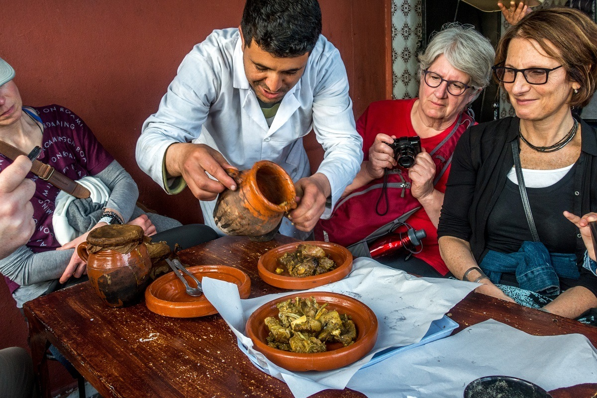 Man serving traditional Moroccan tangia meat on pottery