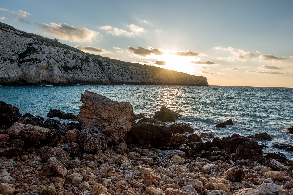 Sunset over the cliffs and water of Fomm ir-Rih Bay