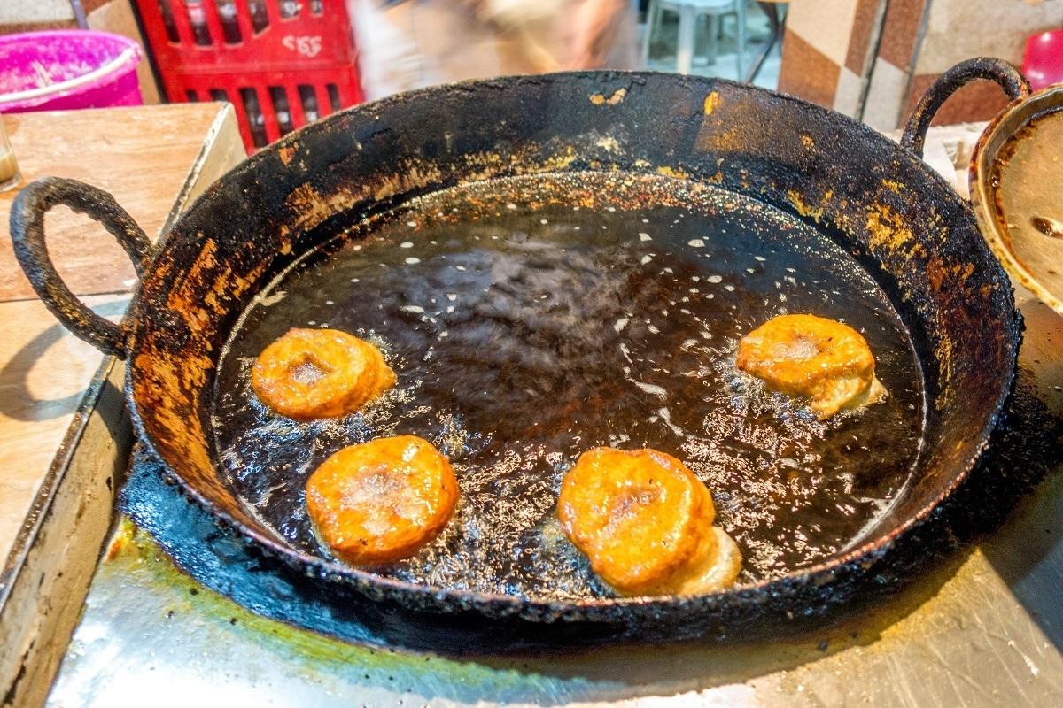Sfenj, a donut-like treat, frying in oil
