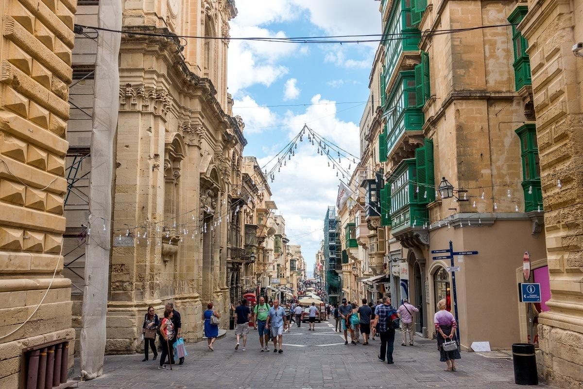 People walking down a street in Valletta