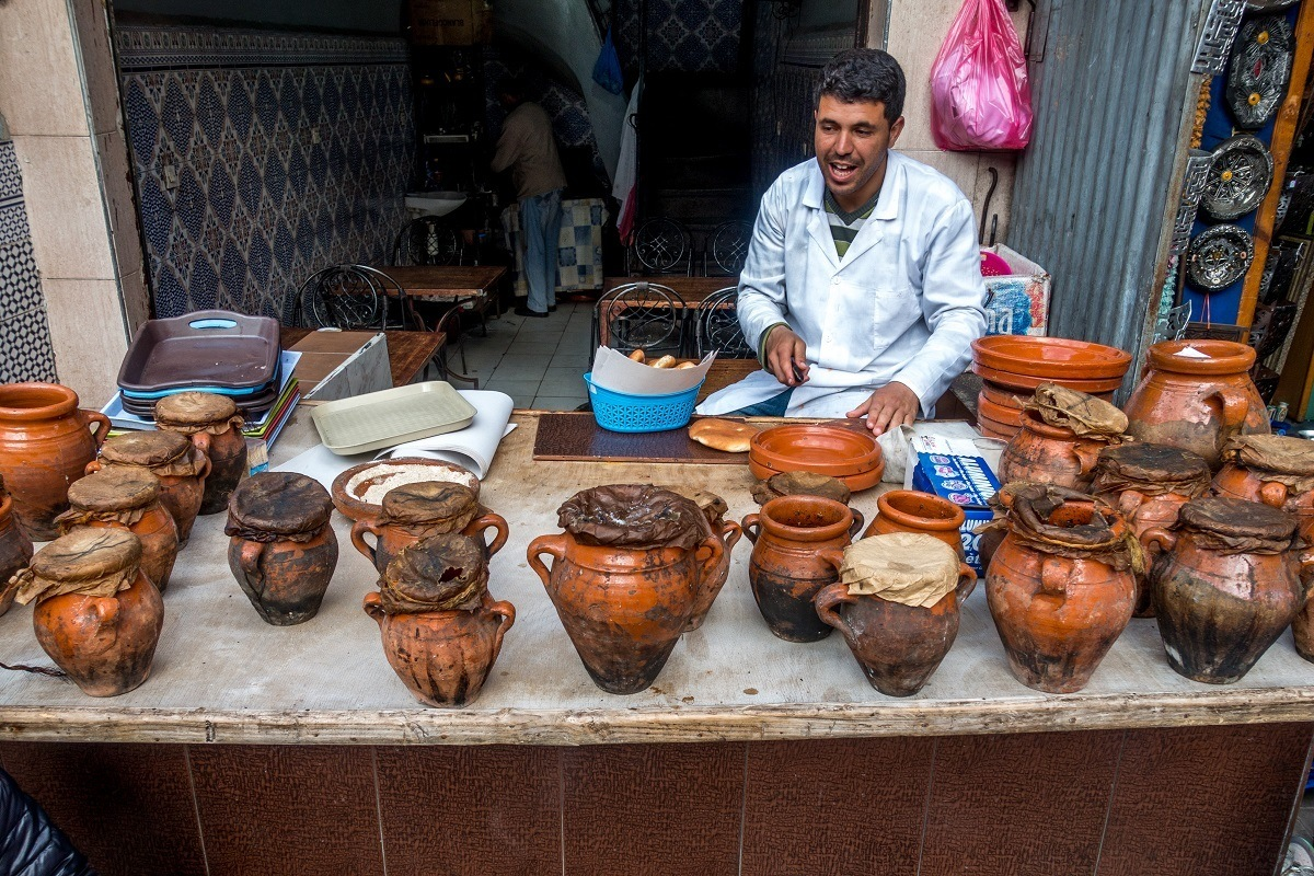 Man with clay pots on table at a restaurant