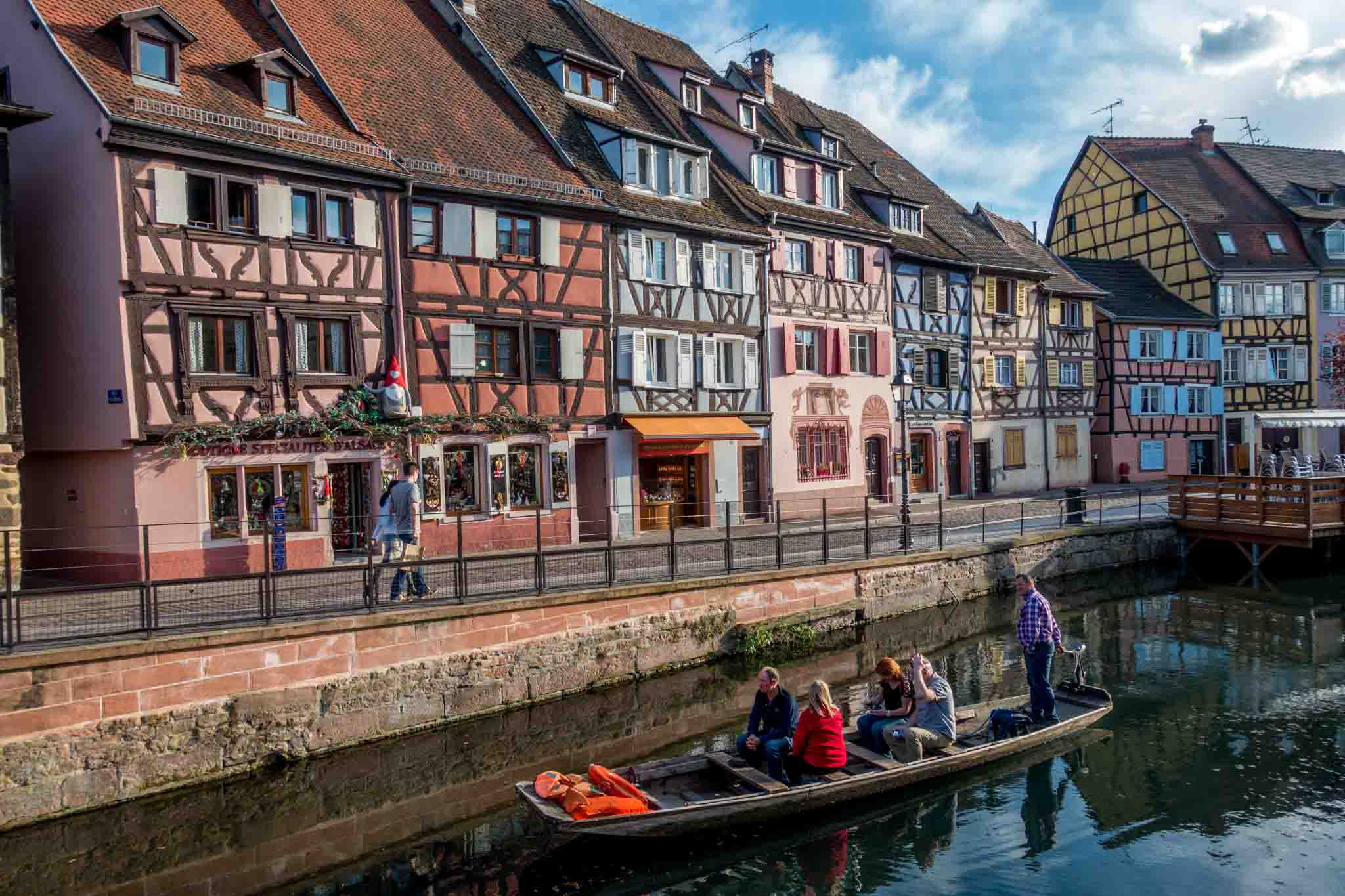 Boat floating by the colorful buildings of Colmar