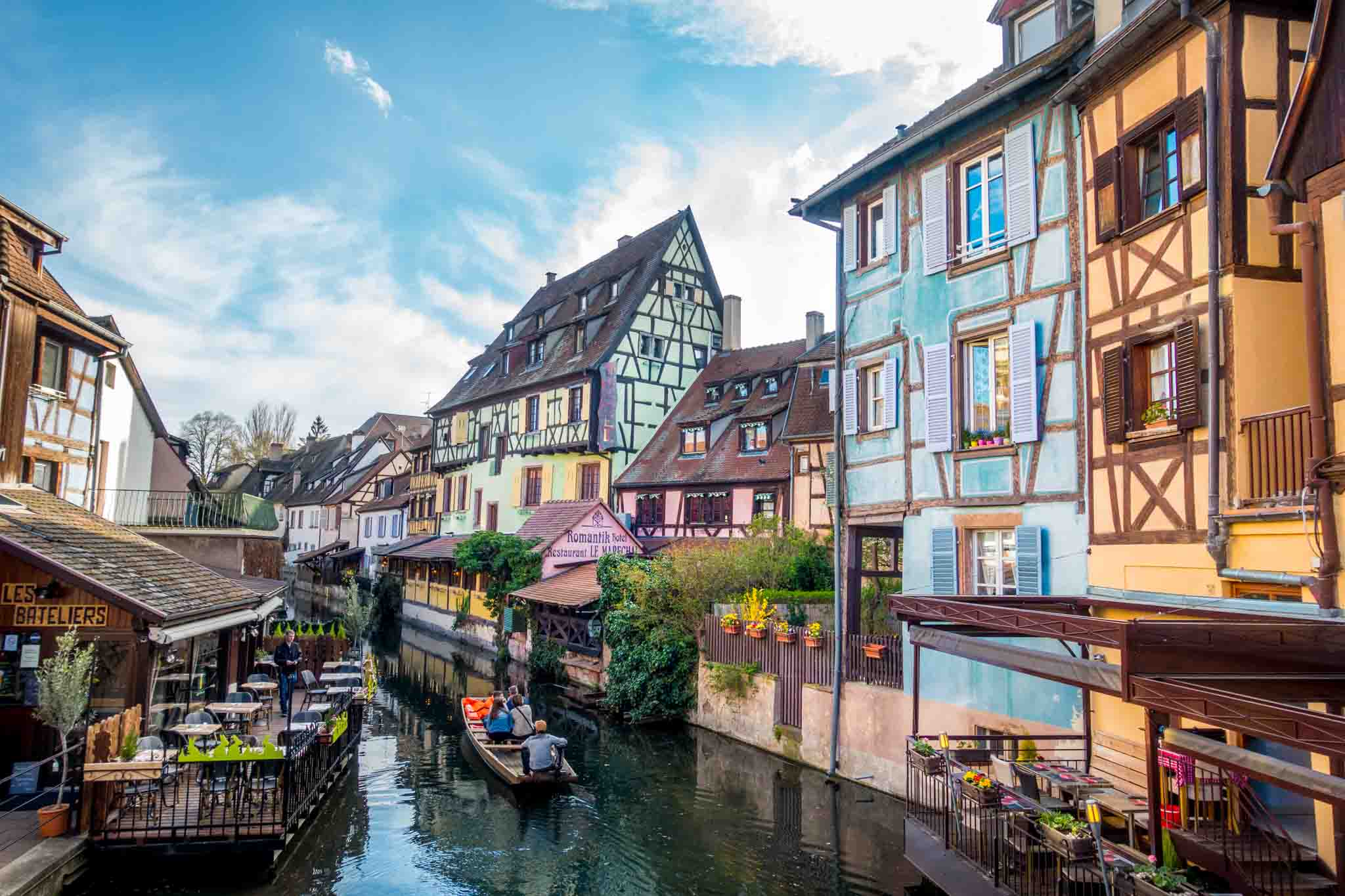 Boat floating past colorful buildings in Petite Venise in Alsace