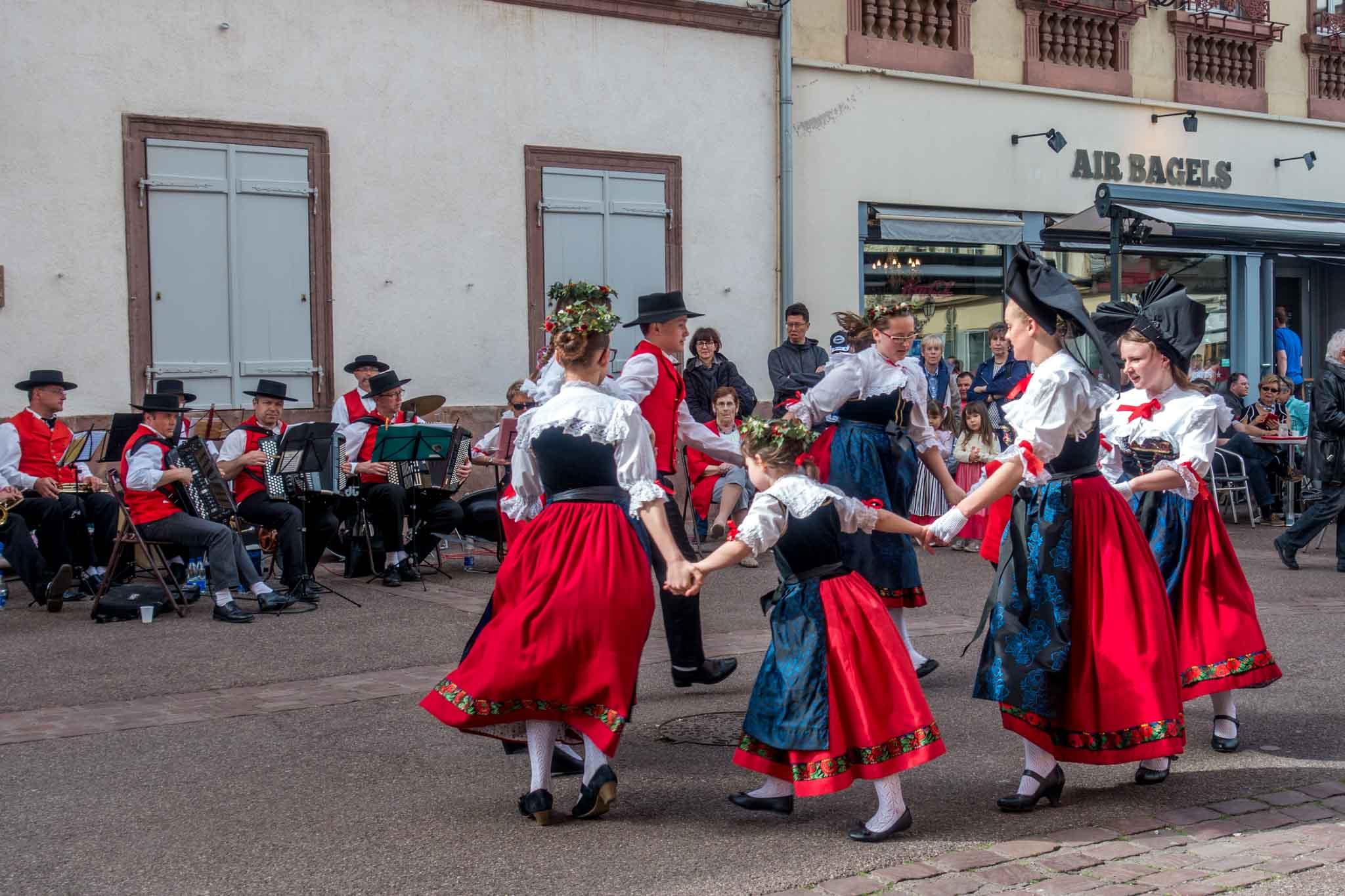 People dancing in traditional Alsatian clothing