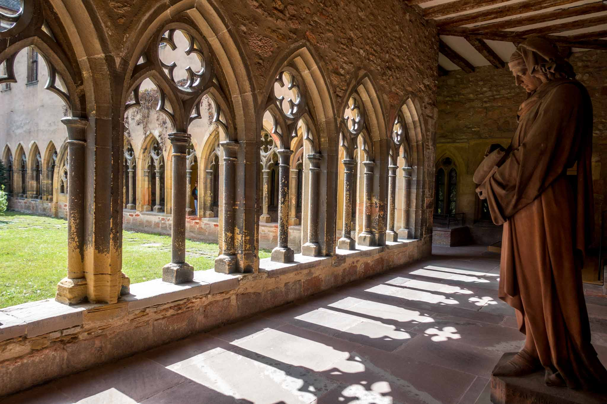 Statue in cloisters with arched windows