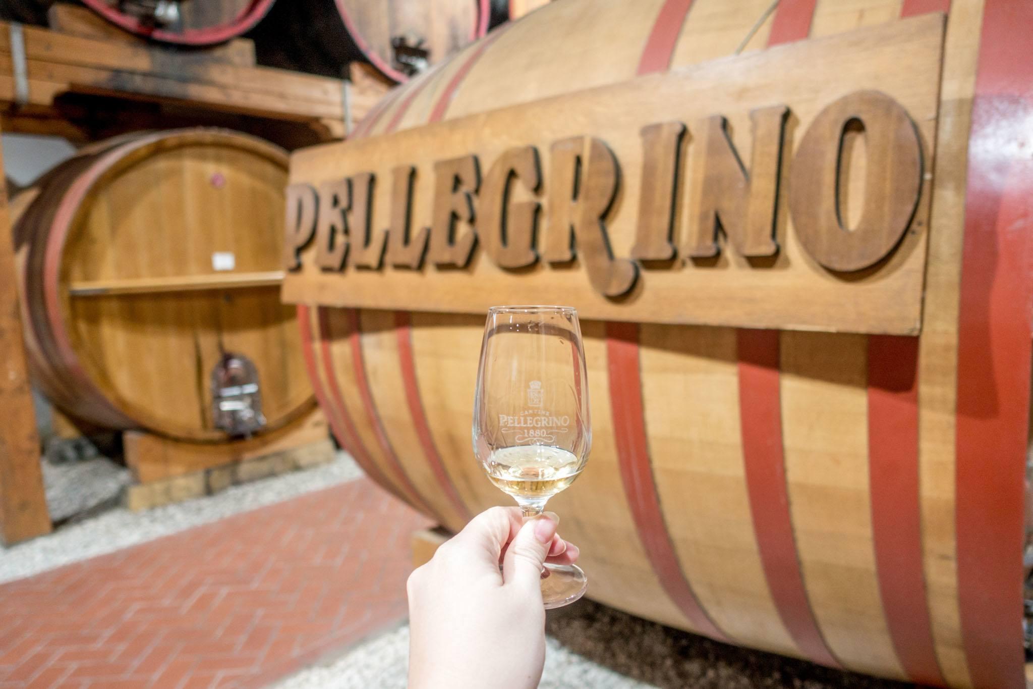 Glass of Marsala wine near wine barrel at Cantine Pellegrino