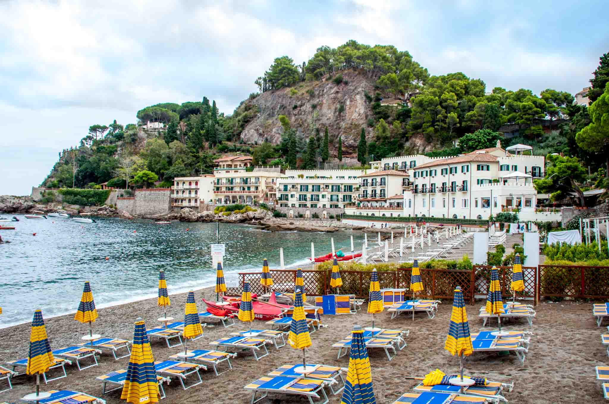 Chairs and umbrellas on a beach beside a hotel