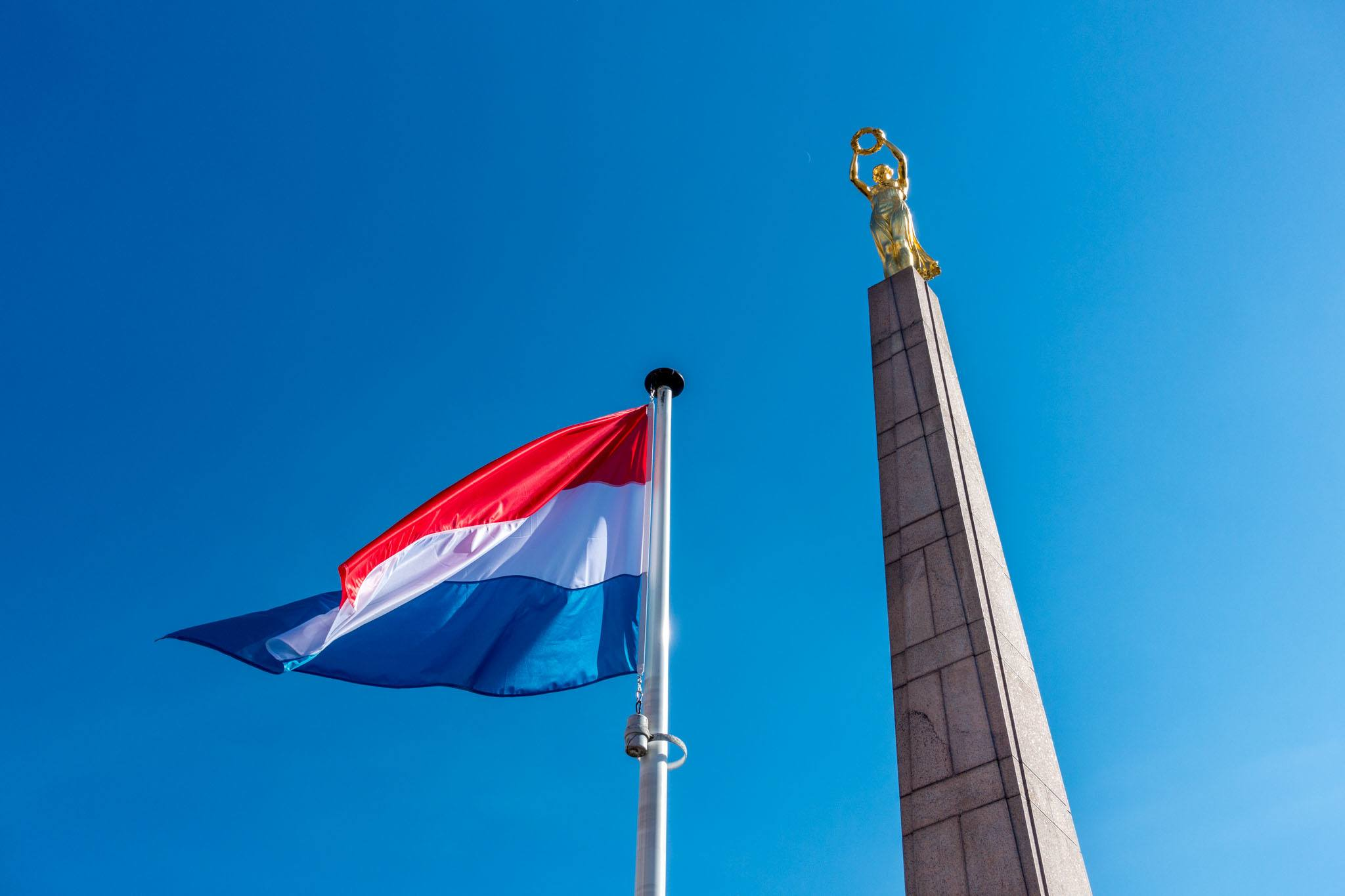 Golden statue of a woman holding a wreath next to the Luxembourg flag