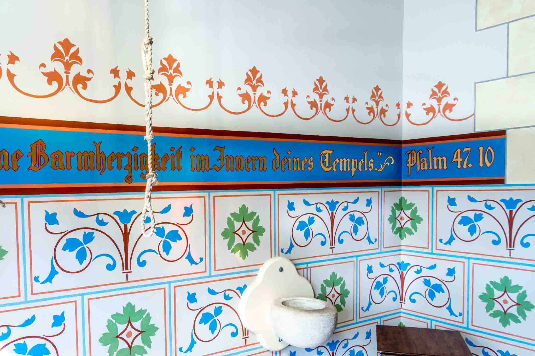 German Bible verse painted on a wall with holy water font