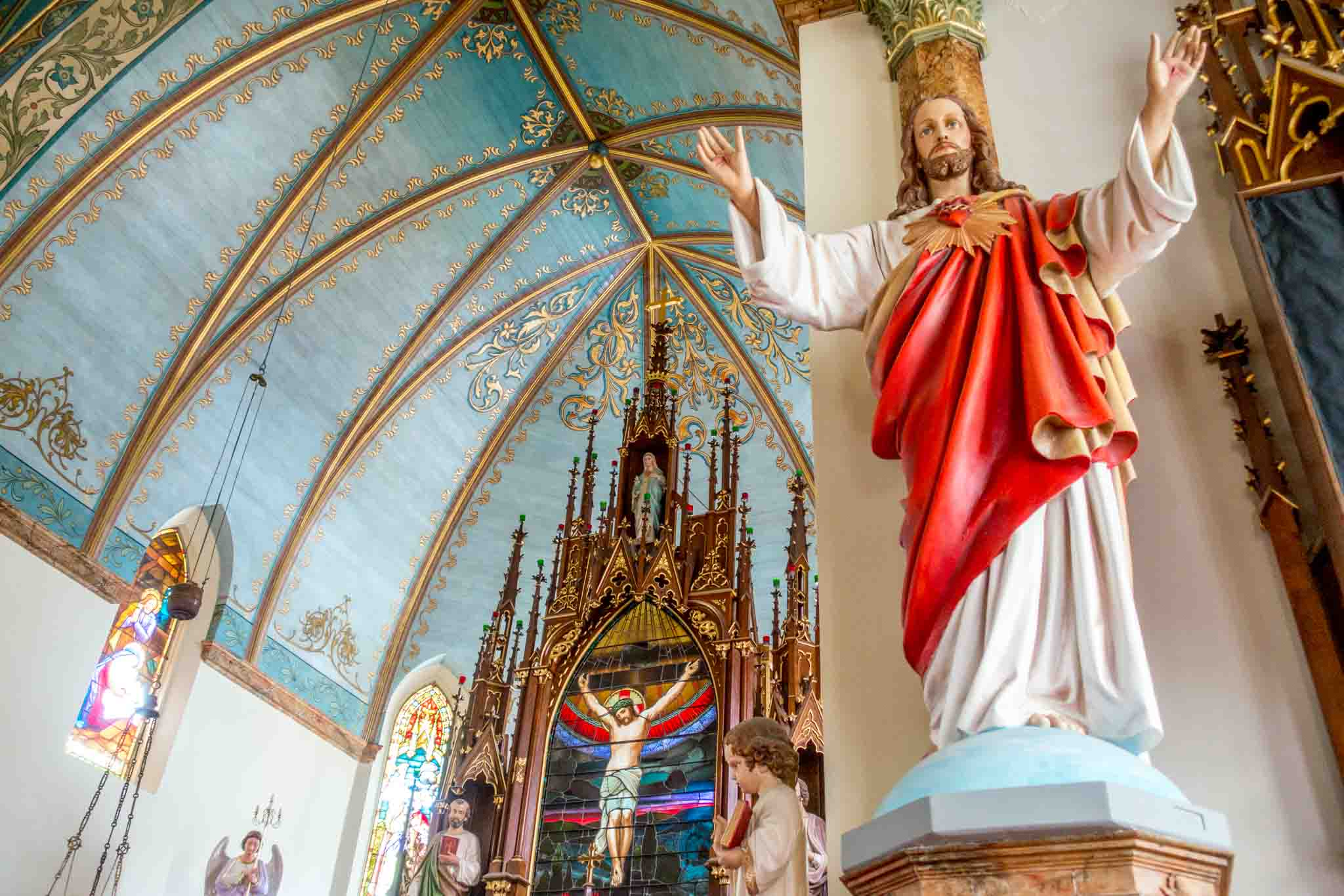 Statue of Jesus with a heart beside an altar