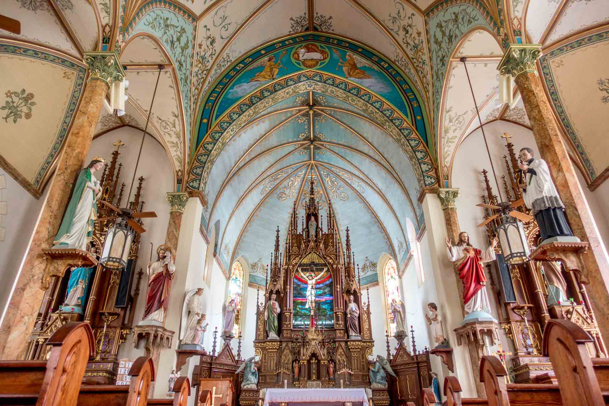 Statues and decorative ceiling in a church sanctuary