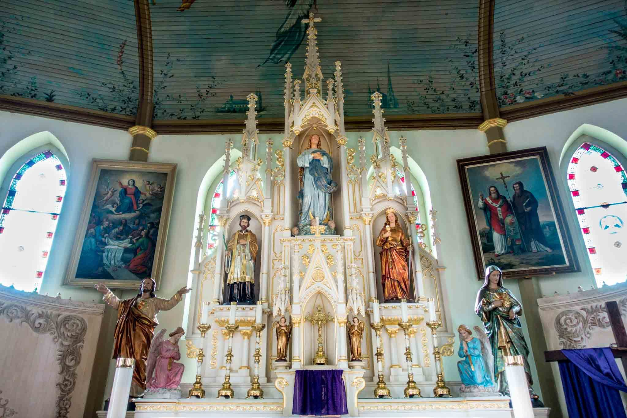 Altar, statues, and turquoise ceiling in church