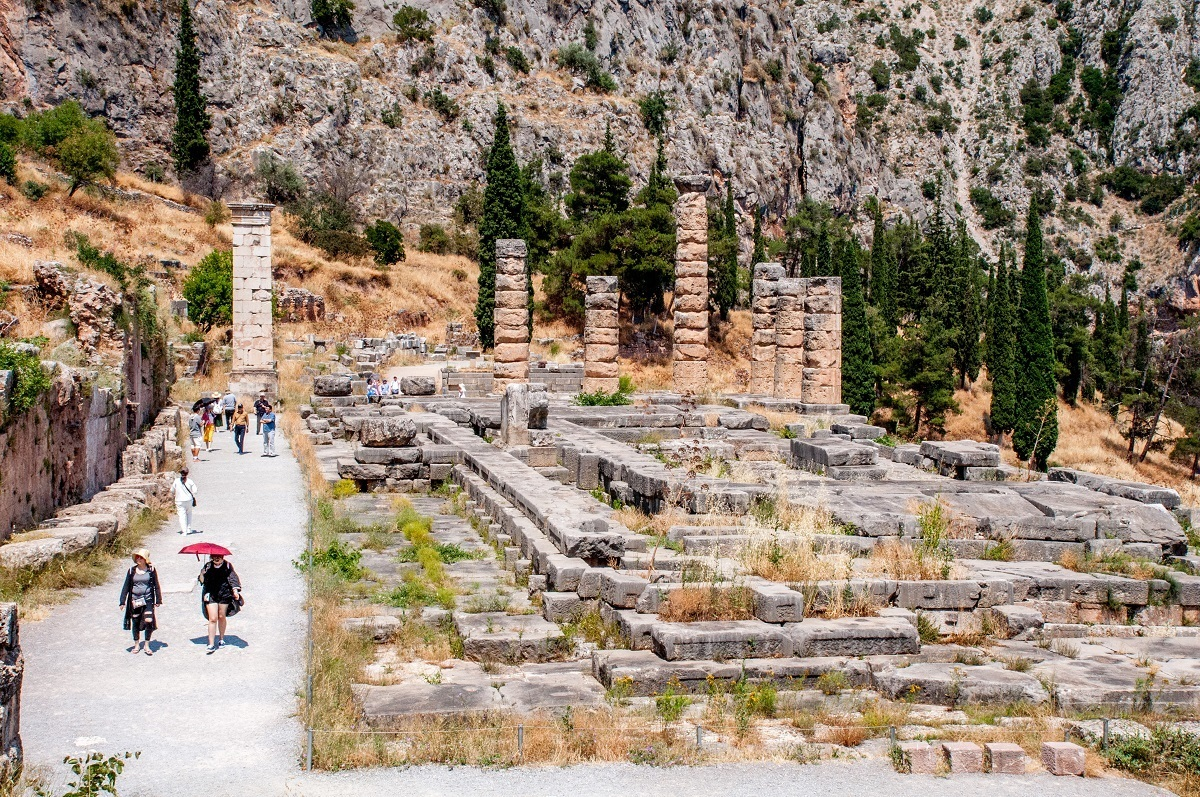 People walking by the Delphi Temple of Apollo in the hot weather