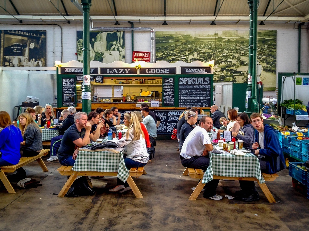 People eating at picnic tables in a market