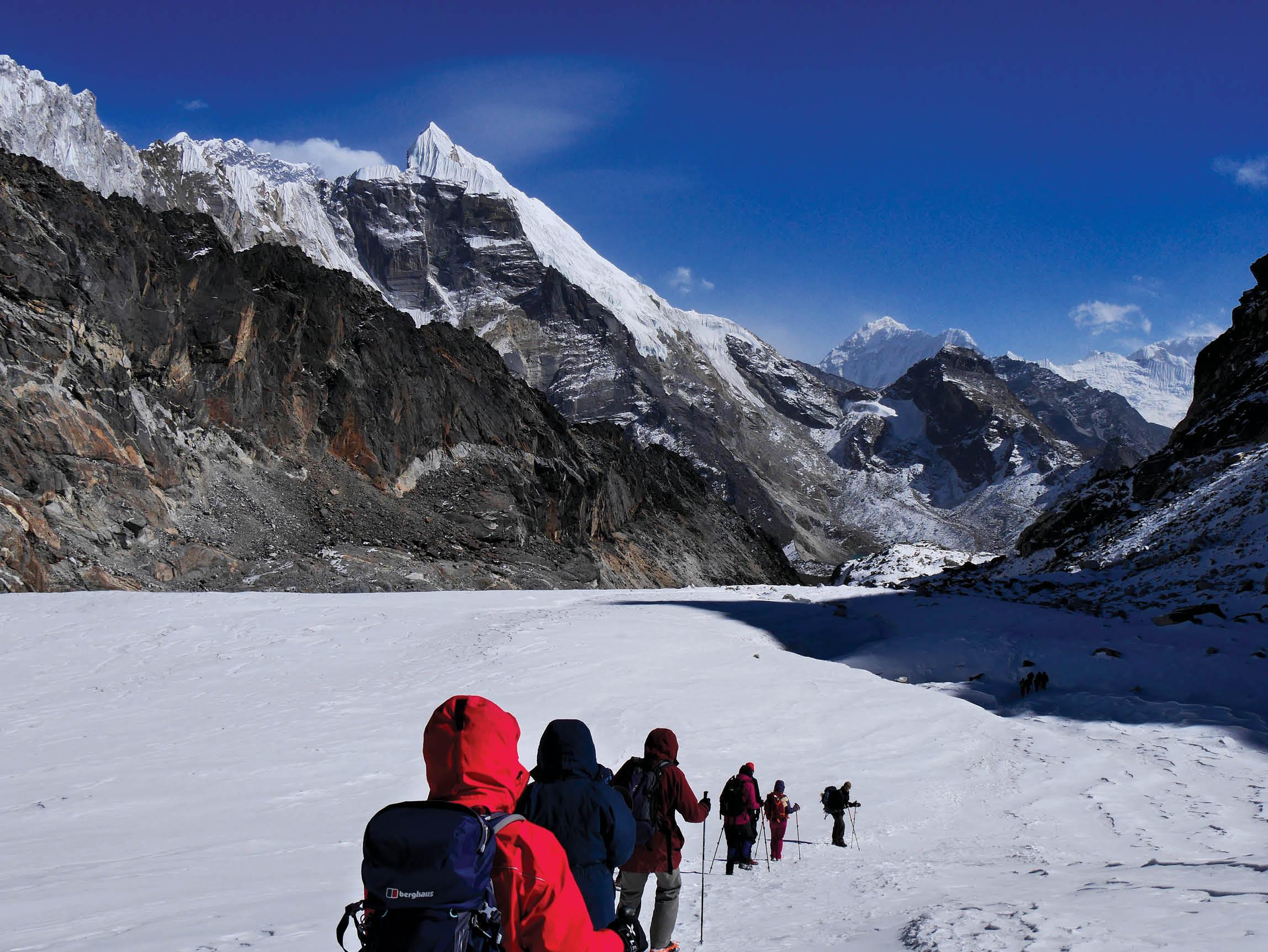 People trekking in Nepal across an ice field.