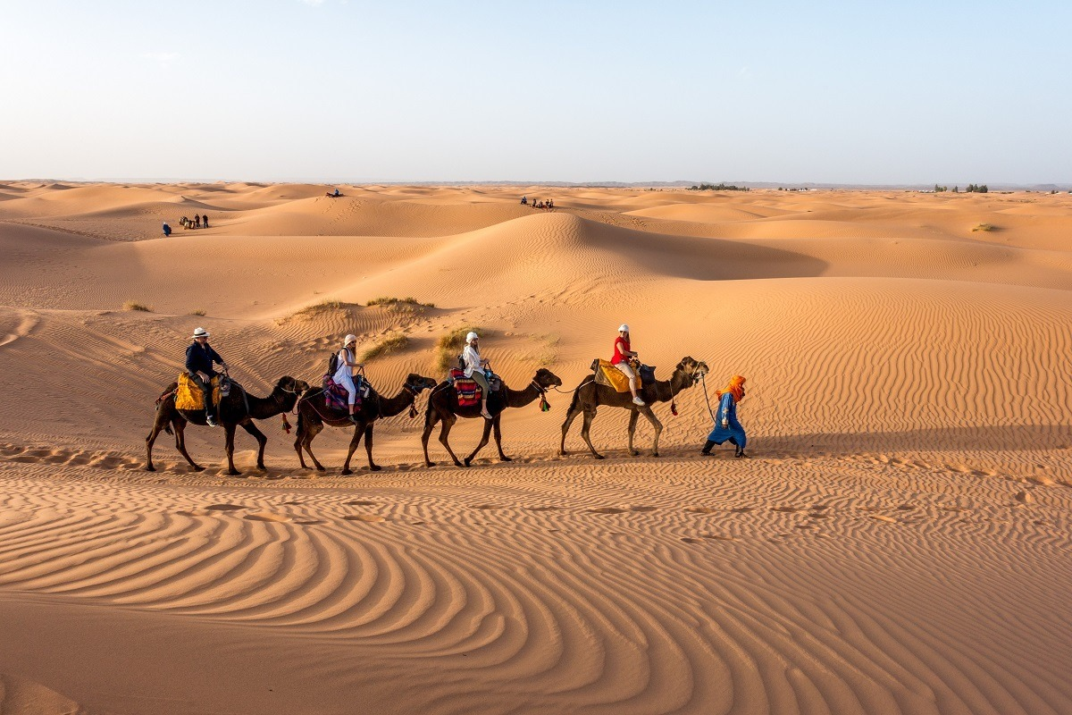 Line of people riding camels across sand dunes in Sahara desert