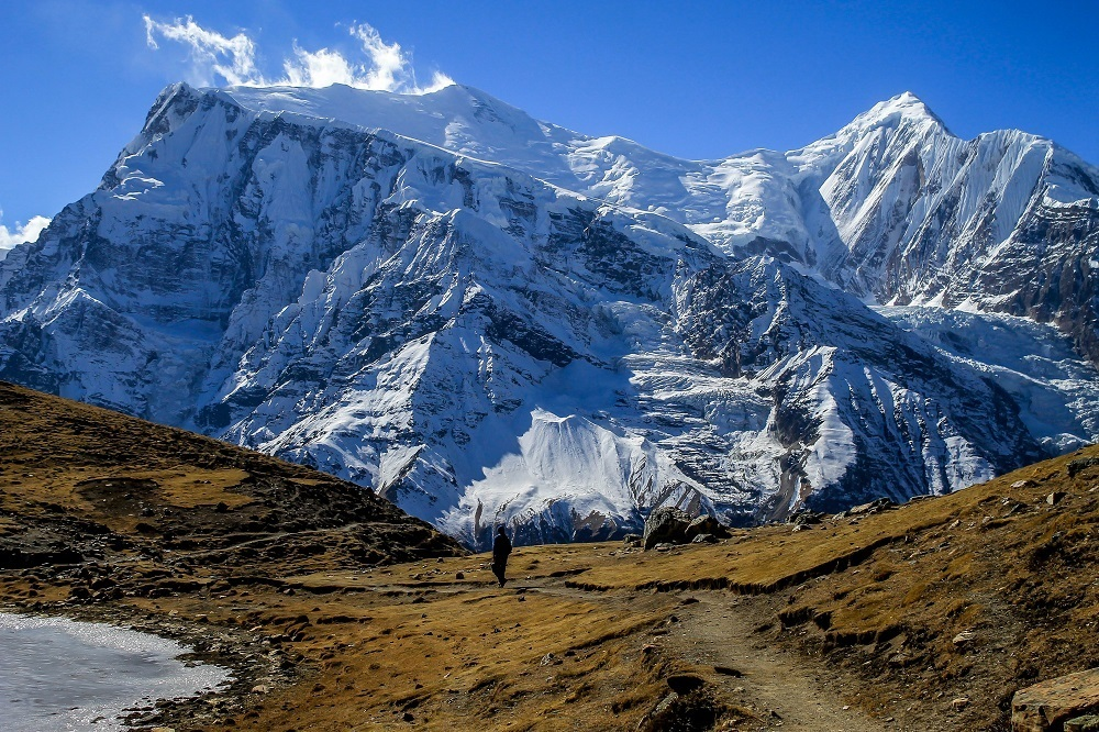 A sherpa walking along a trail leading to a snowy mountain summit
