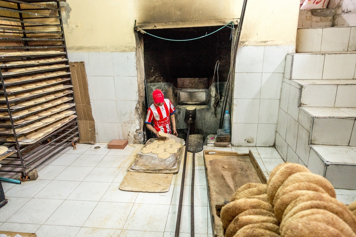 Man baking bread at community bakery in Morocco