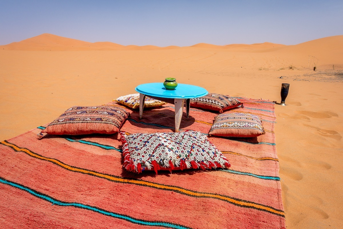 Blanket and table set in sand dune